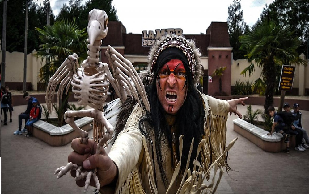 Un Amérindien tient dans sa main un squelette de corbeau