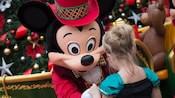 Mickey sert la main à une petite fille déguisée en princesse