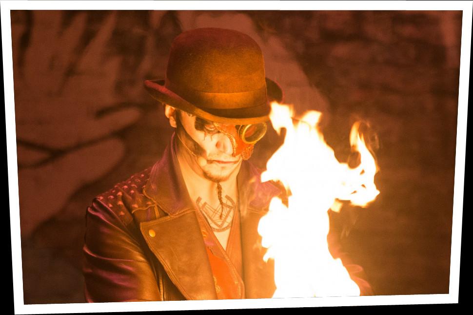 Un homme portant un chapeau regarde une grande flamme située tout près de son visage