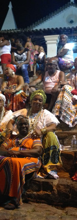 The women of the irmandade sit with visitors at night during the festival to listen to a night full of samba.