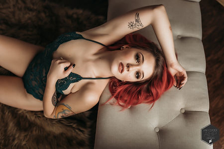 Girl with red hair and green outfit poses on bench
