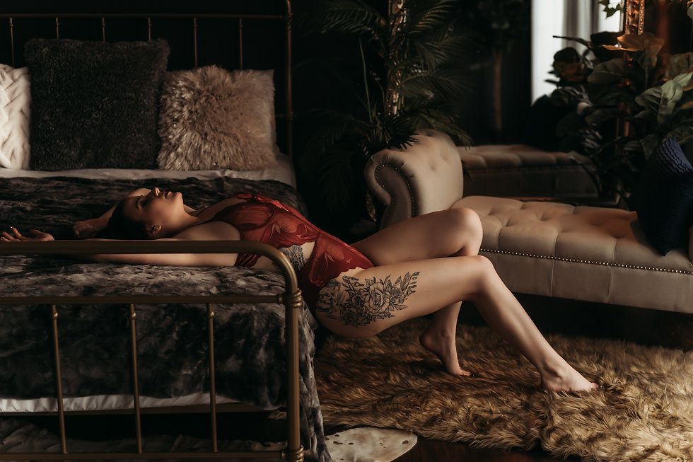 Girl in Burgundy bodysuit stretched across the bed, showcasing her floral tattoo on her leg