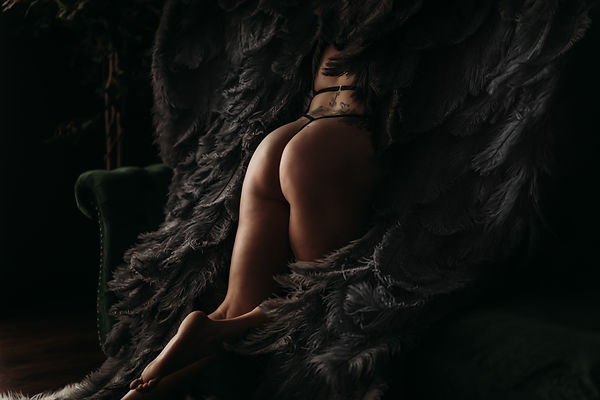 Client showing bare bum posing with grey angel wings leaning on green couch