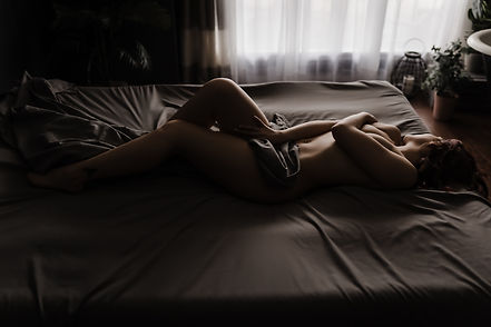 Woman posing nude on bed