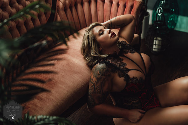 Tattooed Blonde Posing in Black and Red Lace Lingerie on Orange Couch