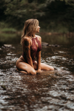 Woman sitting in creek for boudoir images