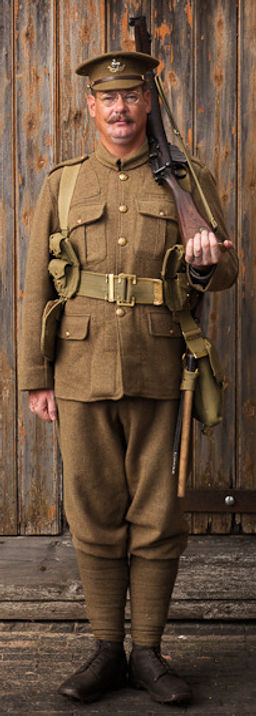 A British Soldier of 1914 prepares to fall in for the march.
