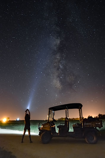 KT shines a light on the Milky Way Galaxy in front of a Kubota parked on a dirt road.