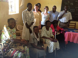 Ugandan women with diverse disabilities, some sitting and some standing, from the Lira district with Catherine and NUWODU staff.