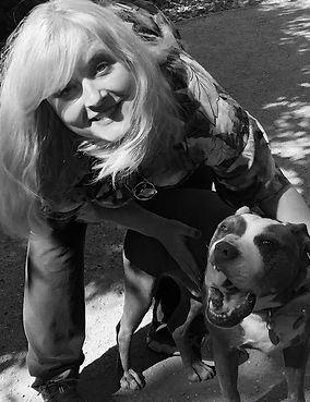 Dog trainer smiles next to a pitbull