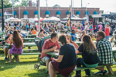 Food venors and people eating at Taste of Muskegon