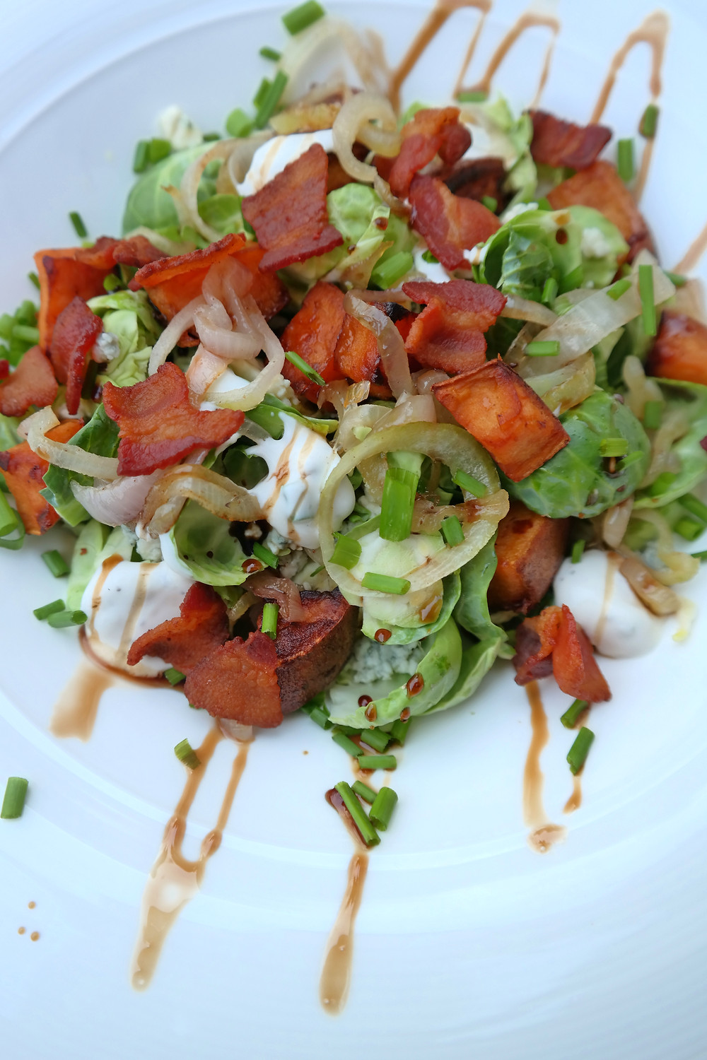 Brussel Salad with sautéed Shallots and Sweet Potato, topped with Crispy Bacon and Balsamic Reduction | eatlovegarlic.com @eatlovegarlic