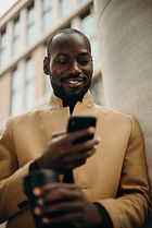smiling-man-looking-at-his-phone-leaning