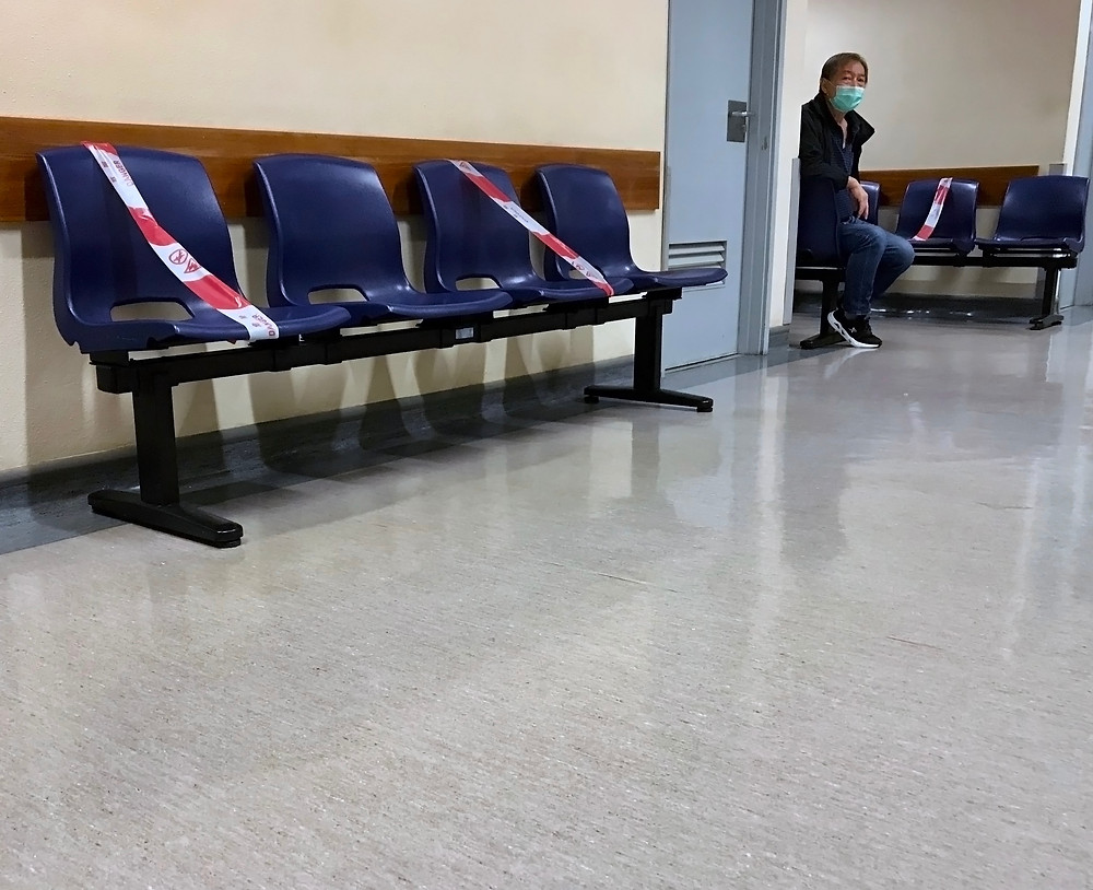 Blocked chairs in a hospital waiting room to promote social distancing during COVID-19.