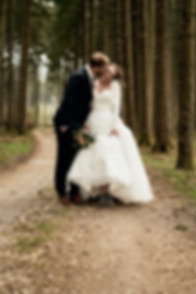 Groom kisses Bride in forest