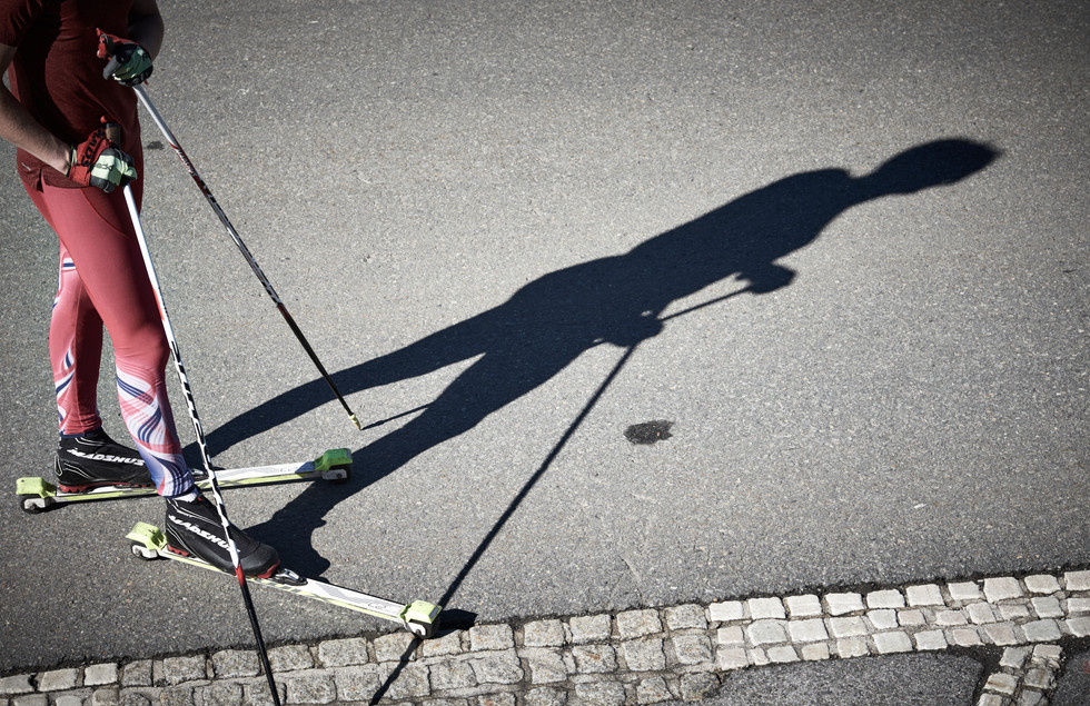 Cross counry skiing, the shadow of an biathlete standing on roller skis at the top of Grossglockner