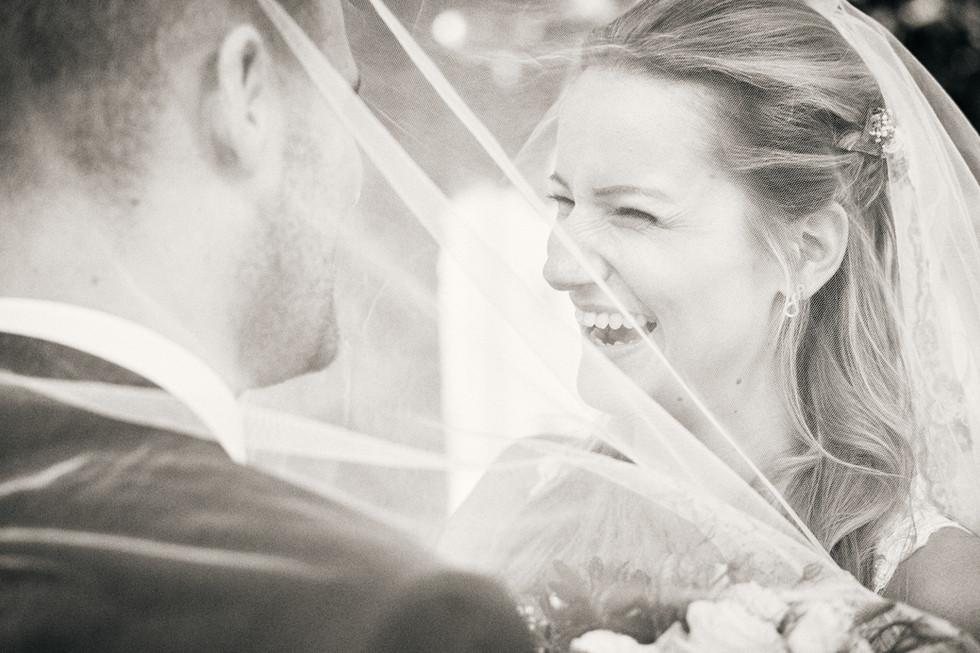 Fotoshooting am Herreninsel, Braut und Brautigam lachen unten schleier.