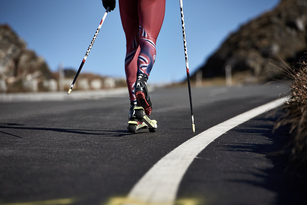 Rollerskiing up Grossglockner, summer training for biathletes on roller skis. Image from behind showing the legs of the athlete