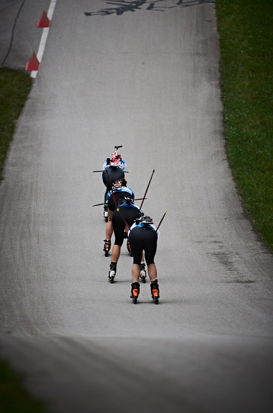 Follow the leader. Bithletes on a downhill section follow each other during German summer biathlon championships