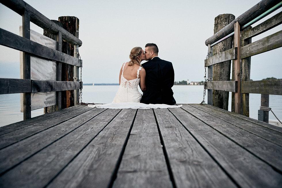 Brautpaar am Steg mit Fraueninsel im Hintergrund. Event Reportage am Fraueninsel und Herrenchiemsee.
