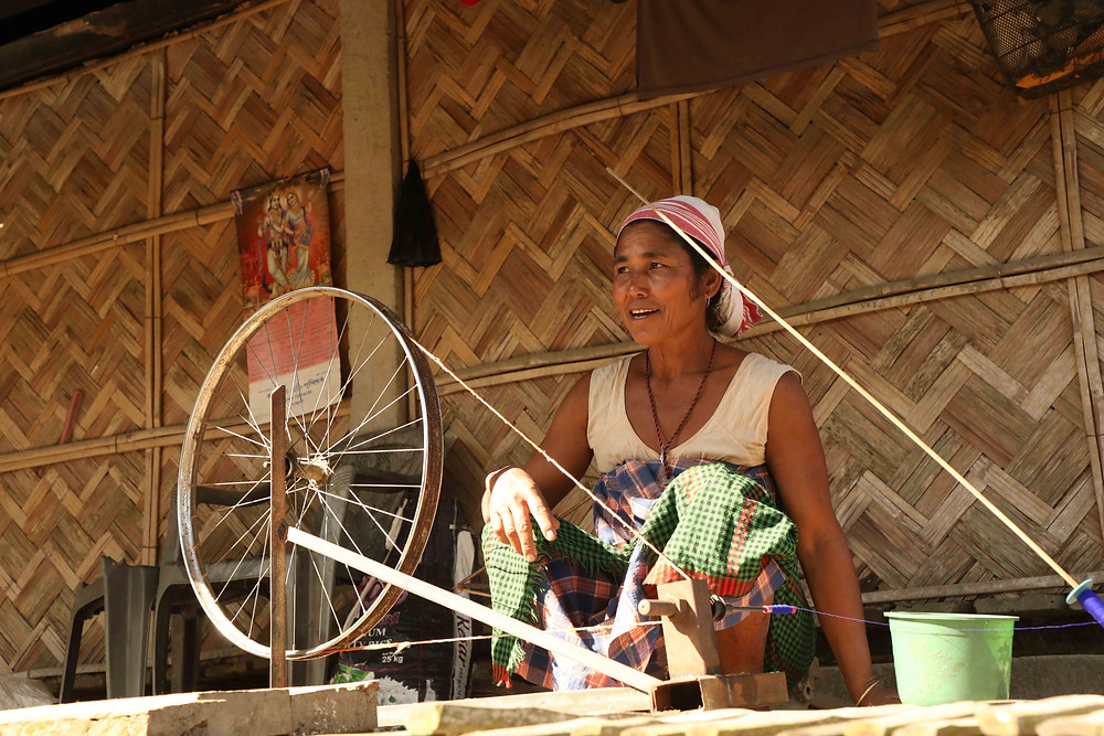 Spinning her yarn outside her house