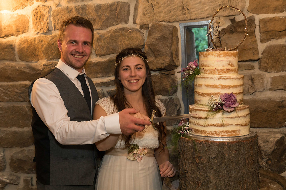 Beautiful wedding photography of the bride & groom cutting their cake