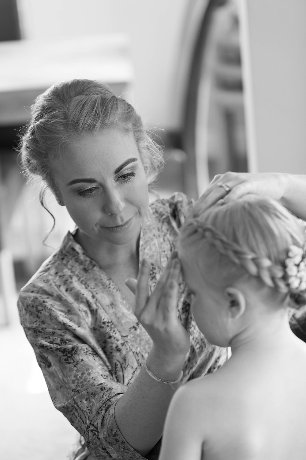 Bridesmaid helps the flower girl to get ready