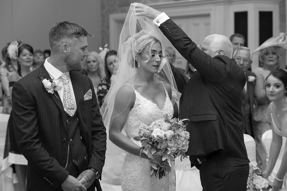 Father of the bride lifting the brides veil