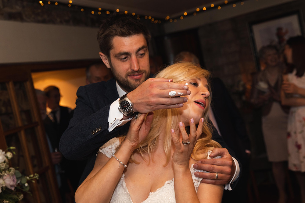 Funny photo of the groom putting cake on the brides face