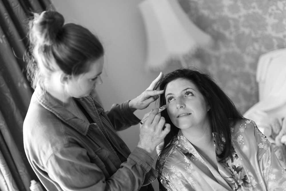 Black & white photograph of the bride having her make up done
