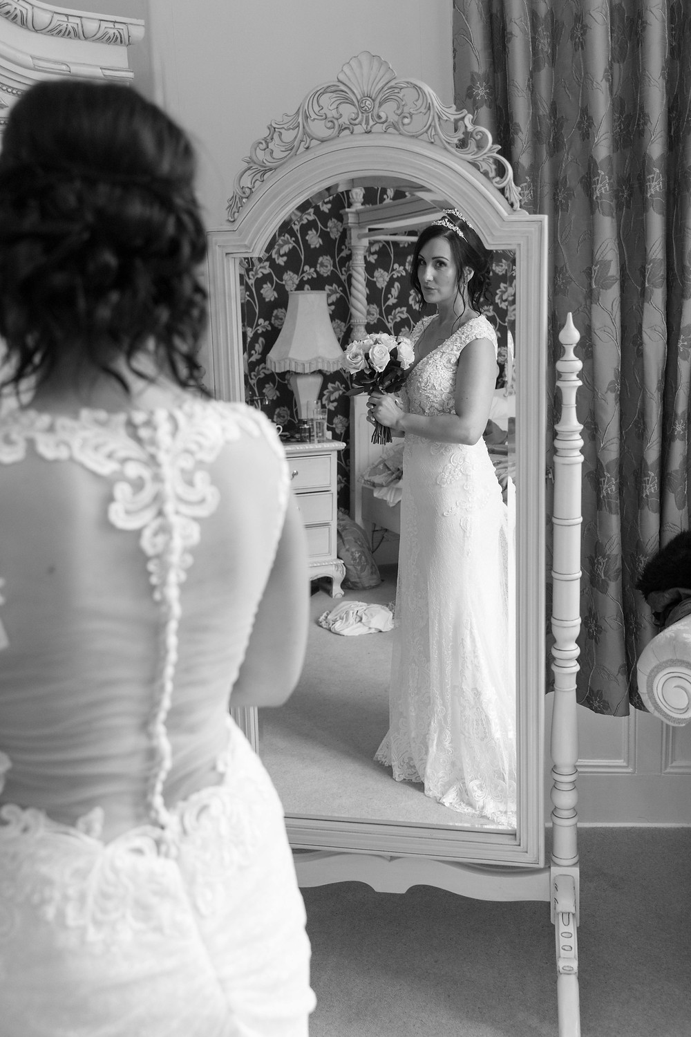 Photo of the bride looking in a mirror