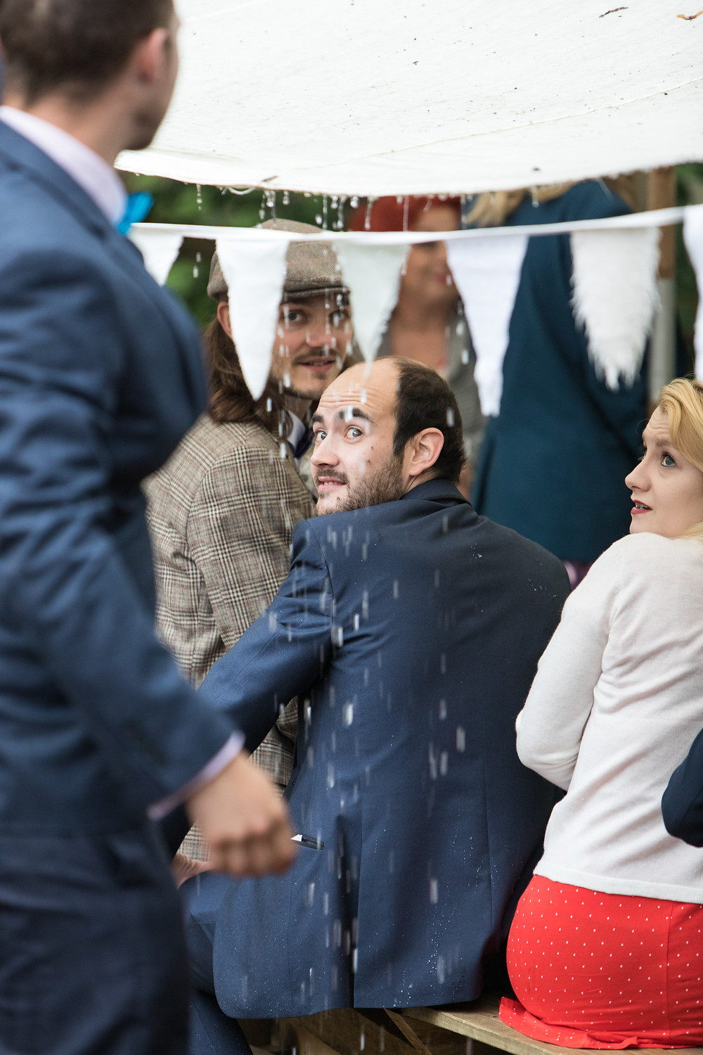 wedding photograph of guest nearly getting wet from the rain