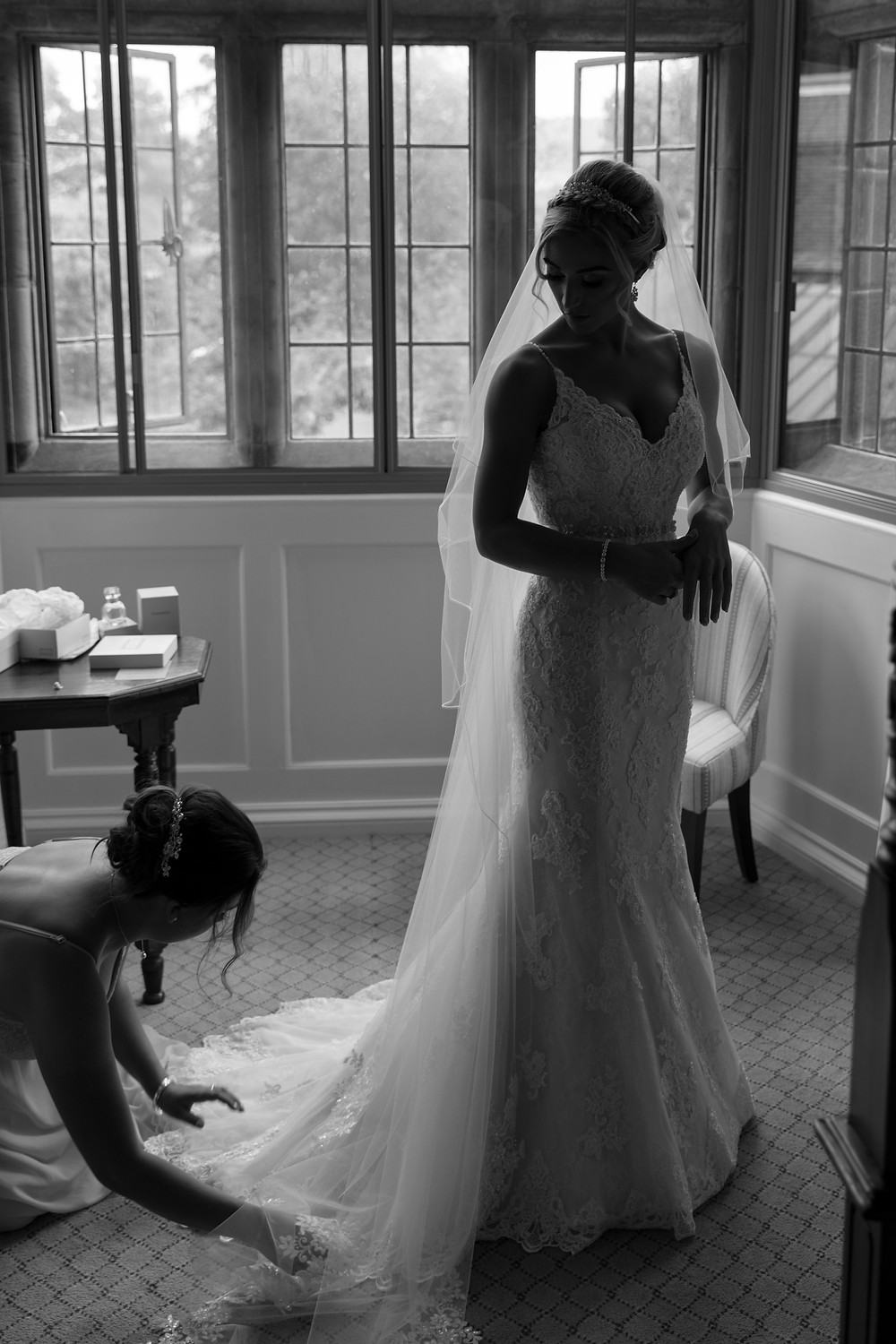Bridesmaid helps the bride with her dress