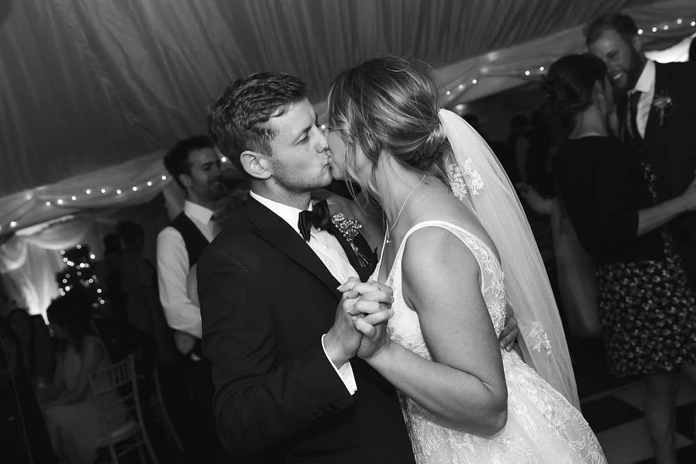 Black and white wedding photo of he bride and groom dancing