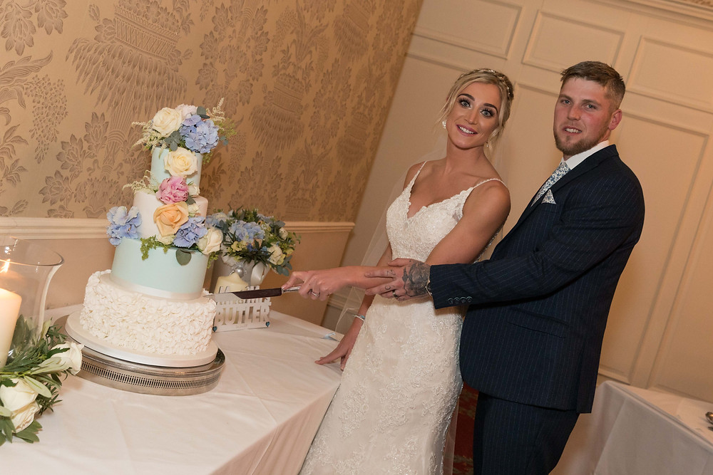 Photograph of the bride & groom cutting the cake