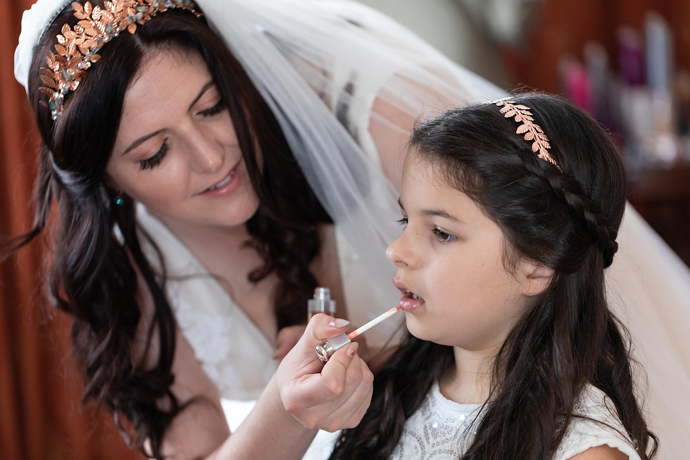 Wedding photograph of the bride helping the flower girl get ready