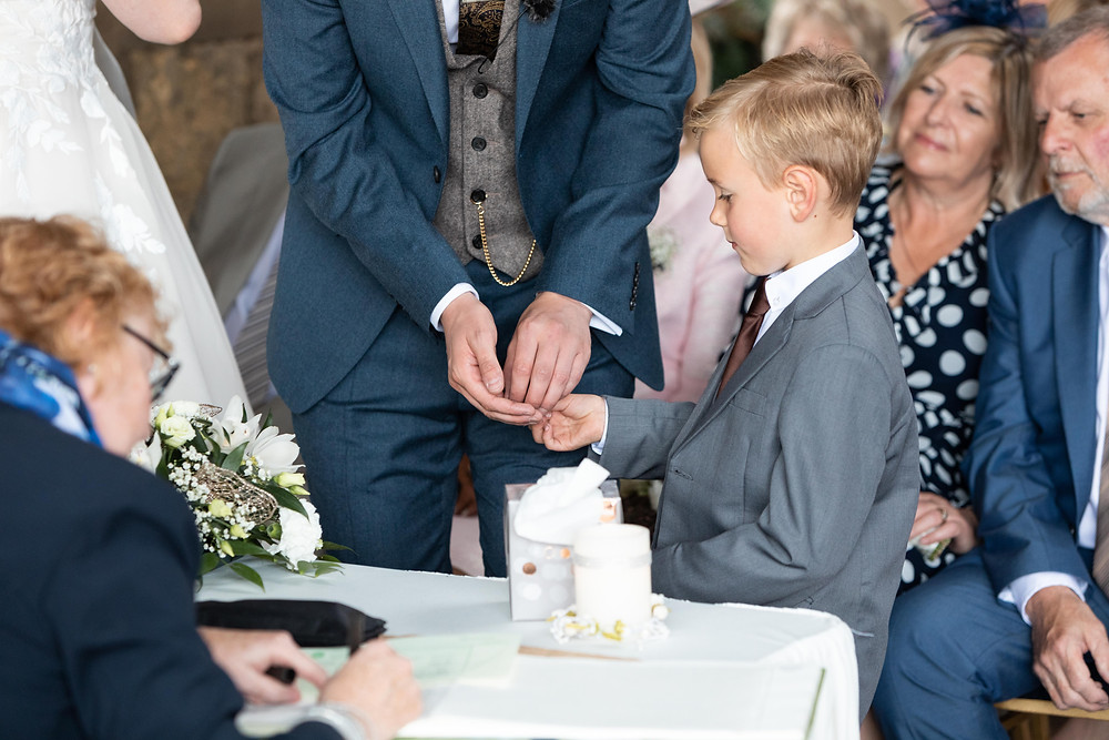 The page boy giving the groom the rings