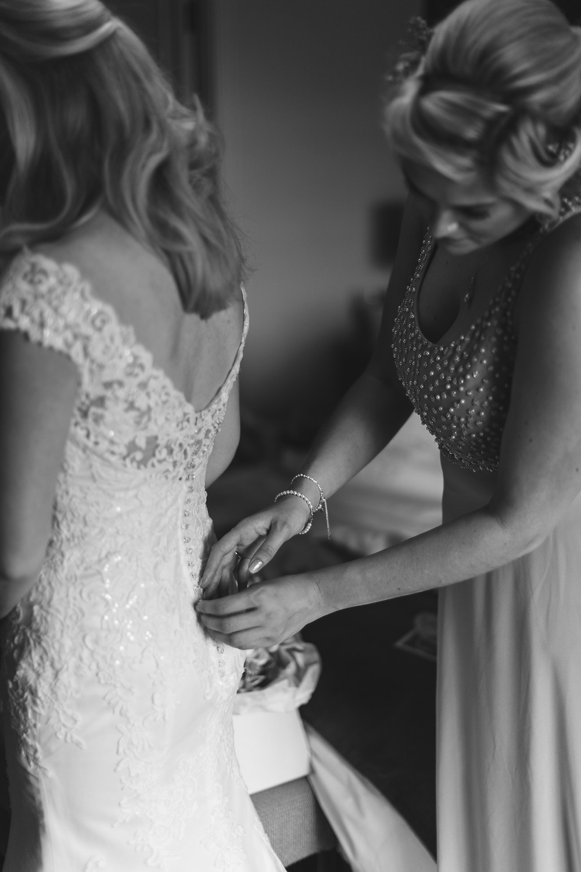 Bridesmaids helping the bride get ready