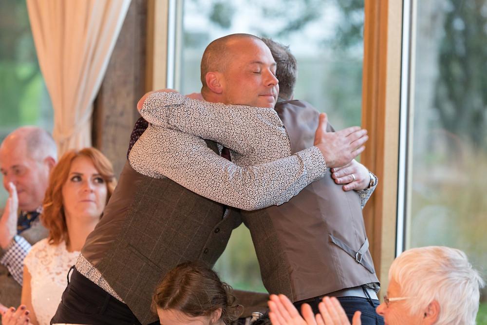 image of the groom & best man hugging