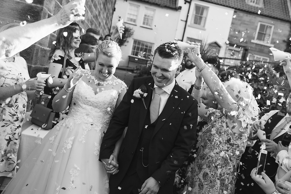 The happy couple surrounded by confetti