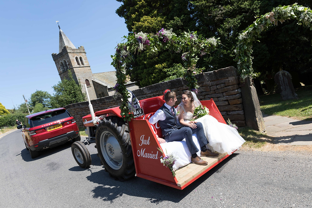 The bride & Groom in a tractor by Whitby wedding photographer