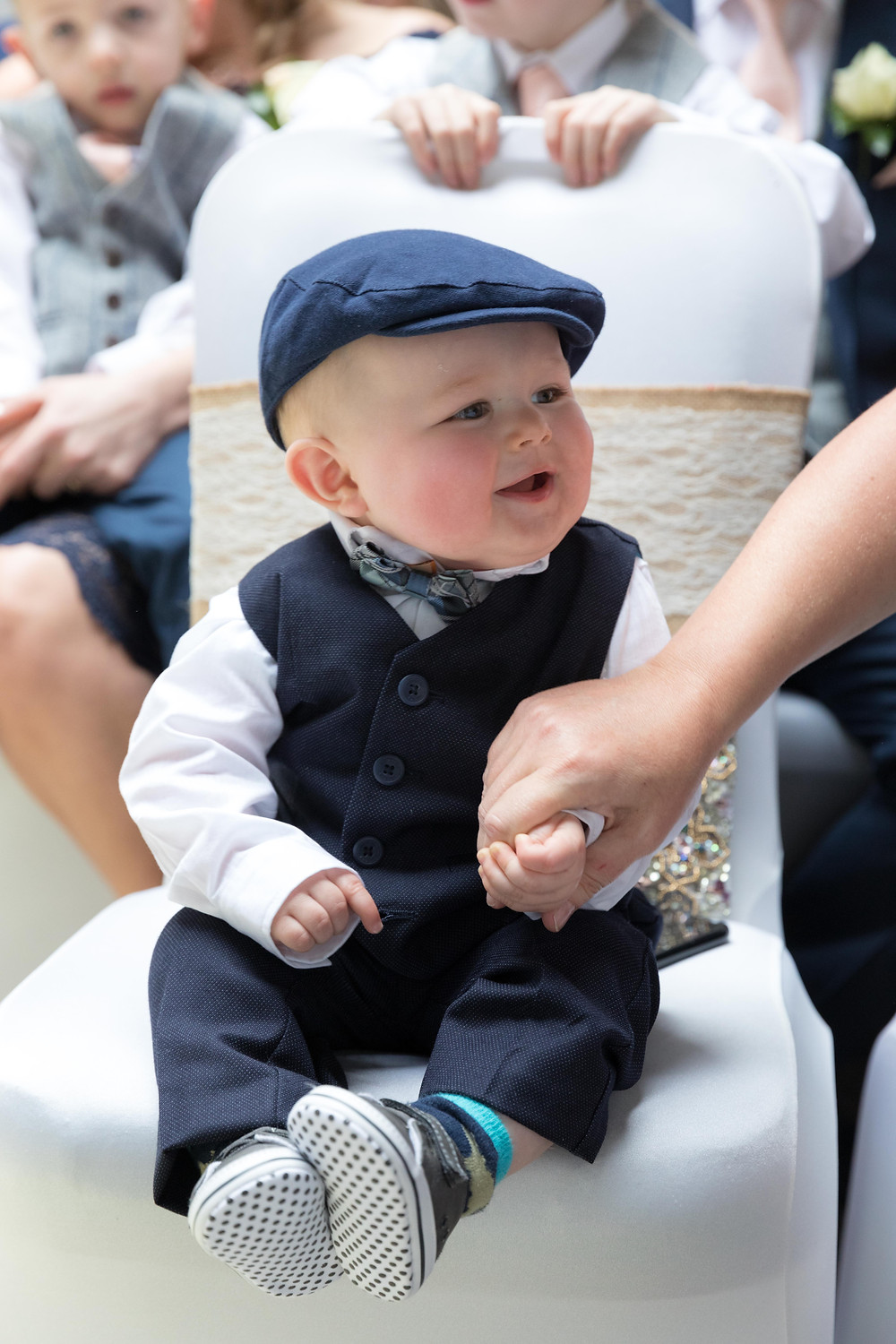 Photo of a baby in a suit during a wedding