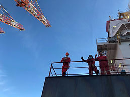 Three masked seafarers on ship with cran