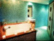 Op maat geleverde badkamerin een penthouse met een blauwe achtergrond met een bad met grote badombouw in een appartement, geheel op maat gemaakt.