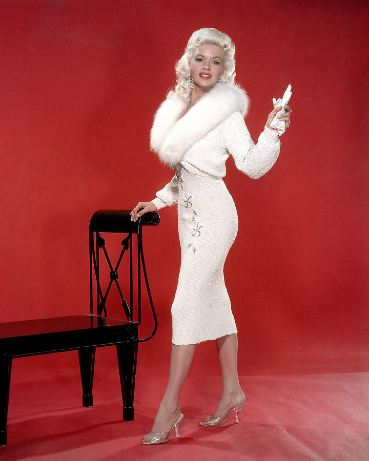 Actress, Jayne Mansfield wearing a white dress and transparent lucite heels standing next to a chair