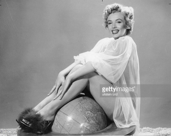Actress, Marilyn Monroe wearing a baby doll dress and furry marabou heels sitting on top of globe