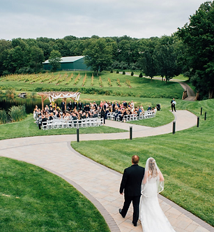 Bride and father walking down the aisle at outdoor waterfront wedding in NJ.