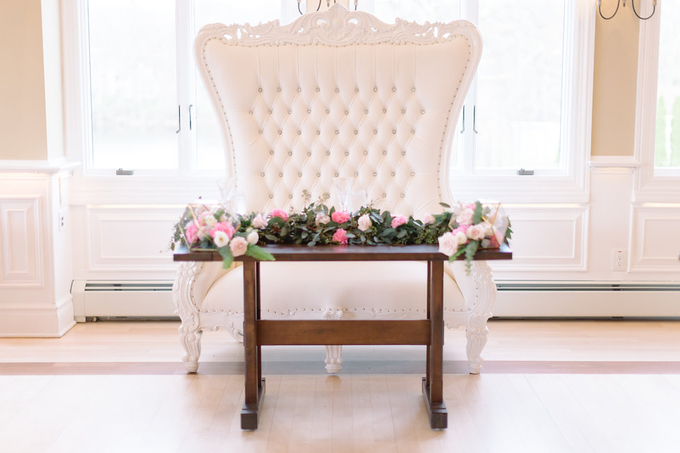 Sweetheart table with a throne chair and spring flowers at elegant wedding venue in NJ.