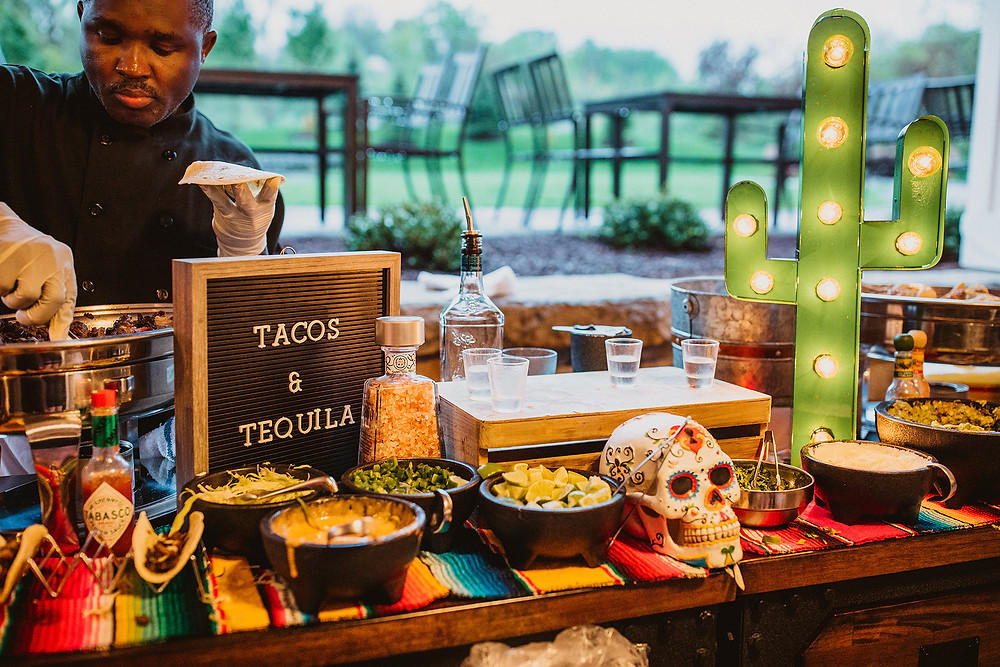 Cocktail hour food station with tacos and tequila with Mexican-themed décor