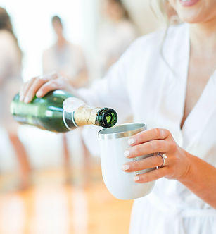 Bride pouring champagne in the bridal suite at rustic wedding venue in NJ.